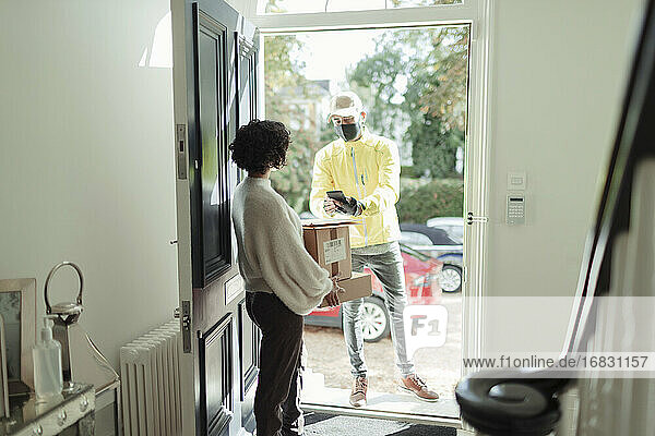 Woman receiving package from delivery man in face mask at front door