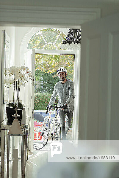Man with bicycle returning home through front door