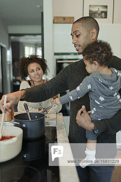 Couple with baby daughter cooking at kitchen stove