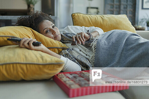 Cozy woman eating chocolates and watching TV on living room sofa