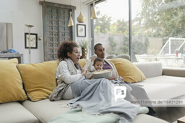 Family watching movie and eating popcorn on living room sofa