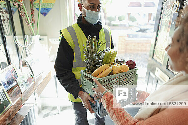 Woman receiving grocery delivery from delivery man in mask