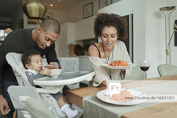 Couple eating spaghetti and feeding baby daughter at dining table