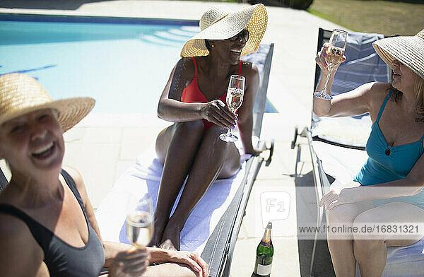 Happy senior women friends drinking champagne at summer poolside