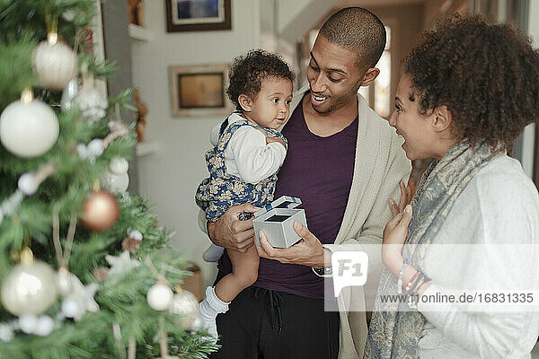 Happy parents and baby daughter opening Christmas gifts by tree