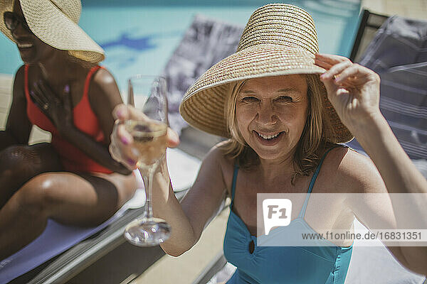 Portrait happy senior woman drinking champagne at sunny poolside