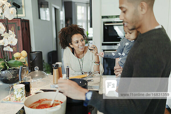 Parents with baby daughter cooking pasta and drinking wine in kitchen