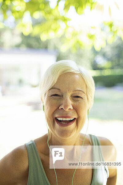 Portrait happy senior woman with headphones in sunny garden