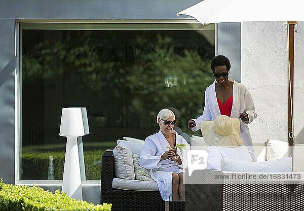 Senior women friends relaxing in spa bathrobes on luxury patio
