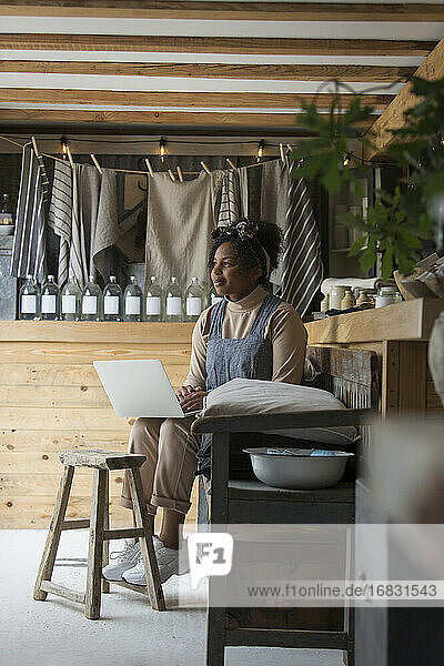 Thoughtful female shop owner using laptop