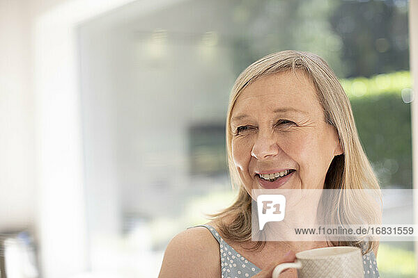 Portrait happy senior woman drinking tea at home