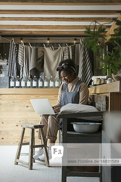 Female shop owner working at laptop in plant nursery