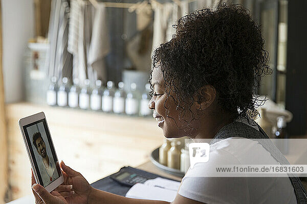 Female shop owner video chatting with friend on digital tablet