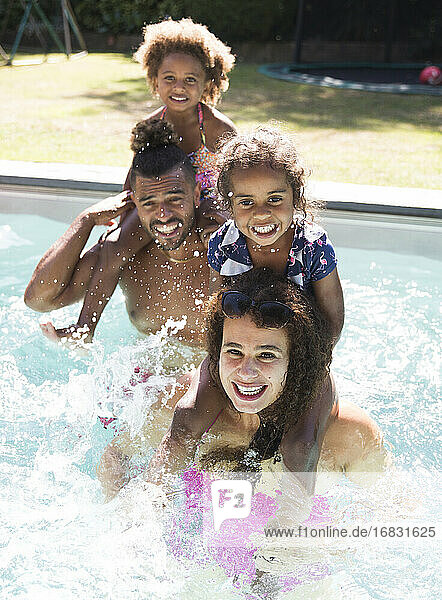 Portrait happy family splashing in sunny summer swimming pool