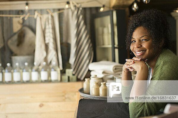 Portrait confident female shop owner at counter