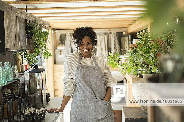 Portrait happy female shop owner in apron in plant nursery