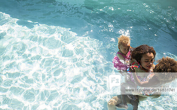 Mother and daughters in sunny summer swimming pool