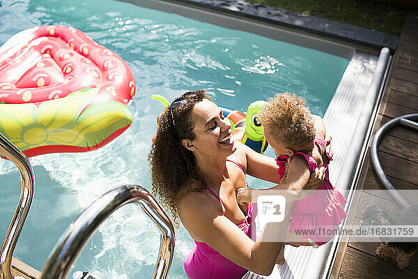 Happy mother lifting daughter into sunny summer swimming pool