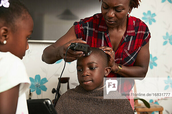 Mother with trimmers cutting son hair in bathroom