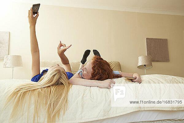 Carefree preteen girl friends taking selfie on bed