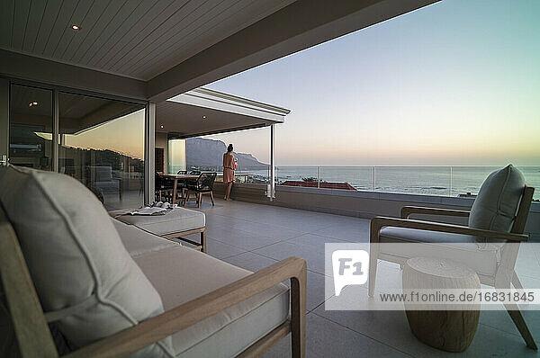Woman relaxing and enjoying scenic ocean view on luxury balcony