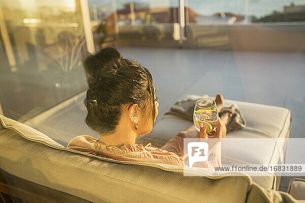 Woman relaxing with water on sunny patio sofa