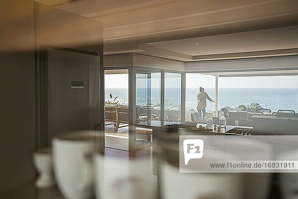 Reflection of woman on sunny luxury balcony with ocean view