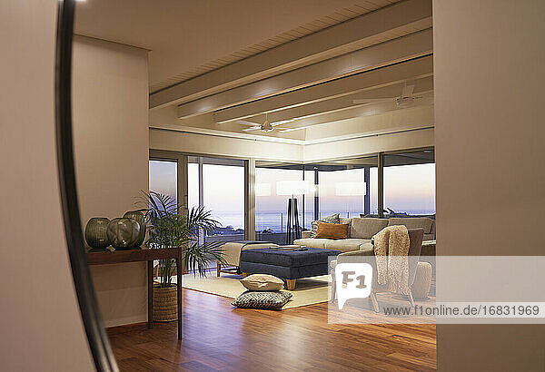 Reflection of luxury home showcase living room with ocean view at sunset