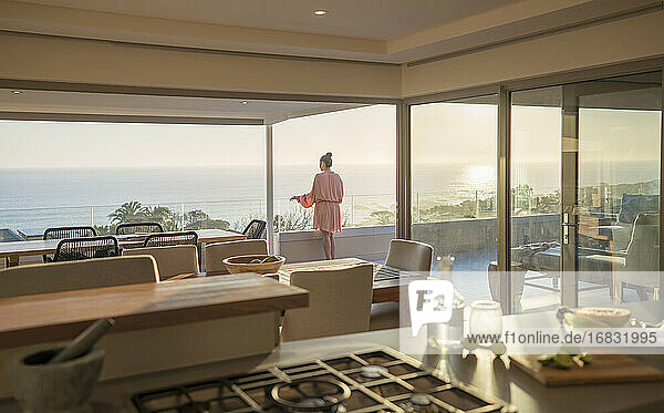 Woman in bathrobe relaxing on sunny luxury balcony with ocean view