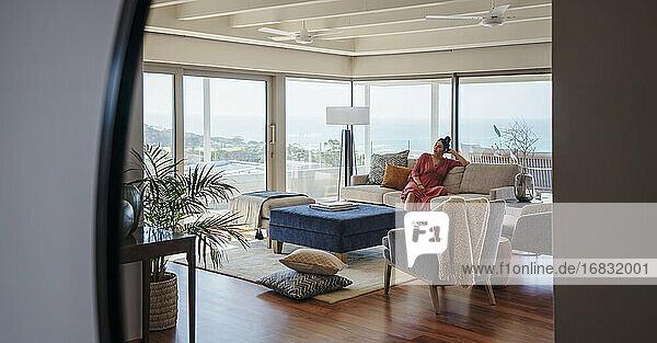 Frau entspannend auf Sofa in Hause Showcase Interieur Wohnzimmer