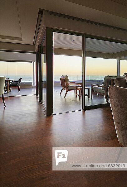 Hardwood floors in home showcase interior with sunset ocean view
