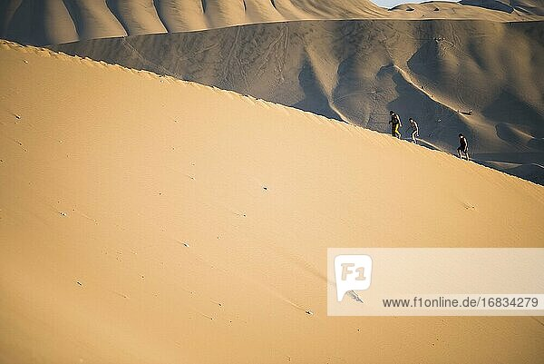 People climbing sand dunes to watch the sunset over the desert at Huacachina  Ica Region  Peru