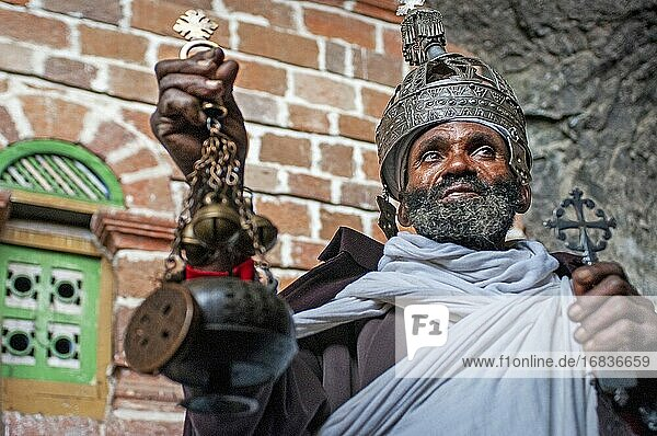 Portrait of an ethiopian orthodox priest holding a cross in nakuto lab cave church  Amhara region  Lalibela  Ethiopia.