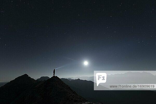 Bergsteiger auf Gipfelgrat mit Vollmond und Sternenhimmel  im Hintergrund Ammergauer Alpen  Reutte  Ammergauer Alpen  Tirol  Österreich  Europa