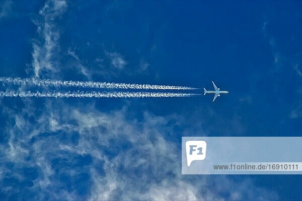 Airplane in flight leaves white contrail lines against a blue sky with light cirrus clouds.