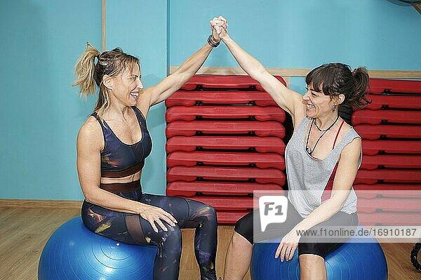 Friends taking break after workout in gym