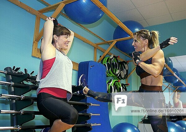 A mid adult woman in his 30s working as a fitness instructor in a gym  helping a freind in her 30s strengthening her arms. They are both Europeans