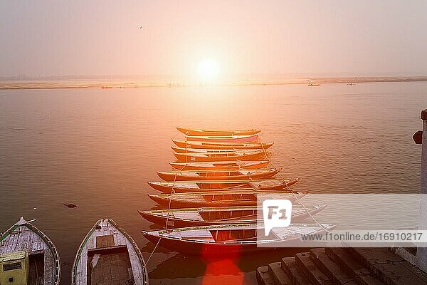 Sunrise over the Ganges river  with tour boats in the foreground in Varanasi  India.