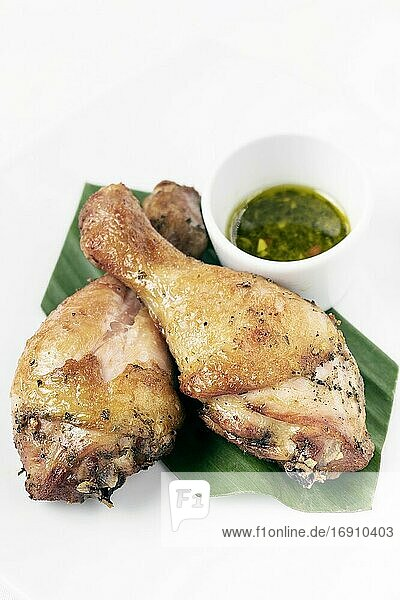 Roast chicken drumsticks appetizer with spicy thai green chilli sauce on white background.
