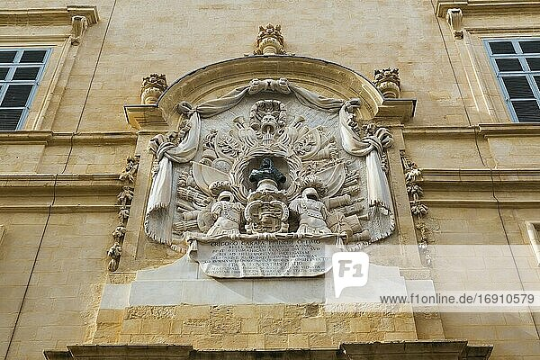 Carved limestone sculptures and architectural details above entrance door on facade of old building  Valletta  Malta.