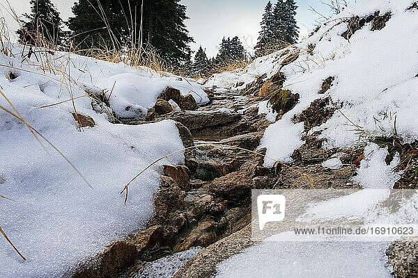 Flowing river water near the snowy road in winter New Year Time.