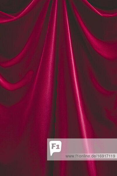 Detail of draped red velvet curtain with folds and creases