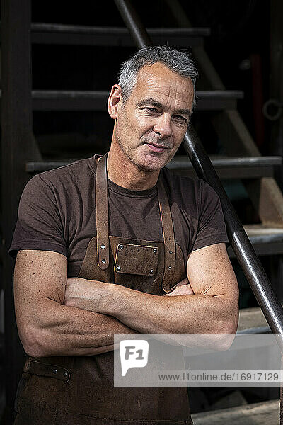 Portrait of male barista with short grey hair  wearing brown apron  arms folded  looking at camera.