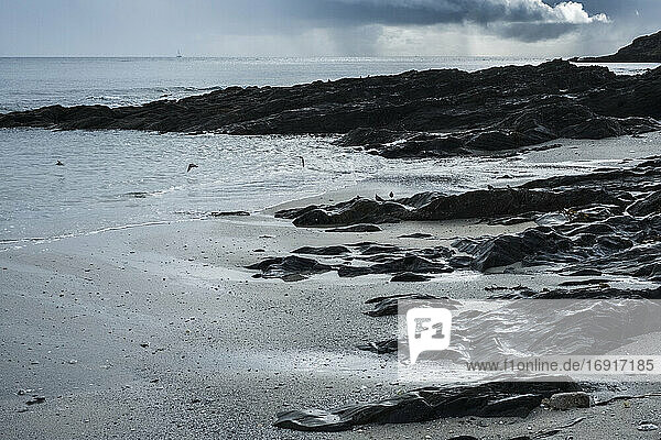View of a sandy beach and rocky shore under a cloudy sky.