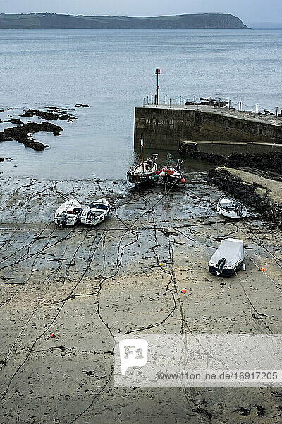 High angle view of fishing boats moored in harbour at low tide.