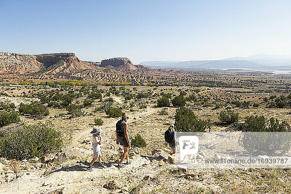 Three people  family hiking on a trail through a protected canyon landscape