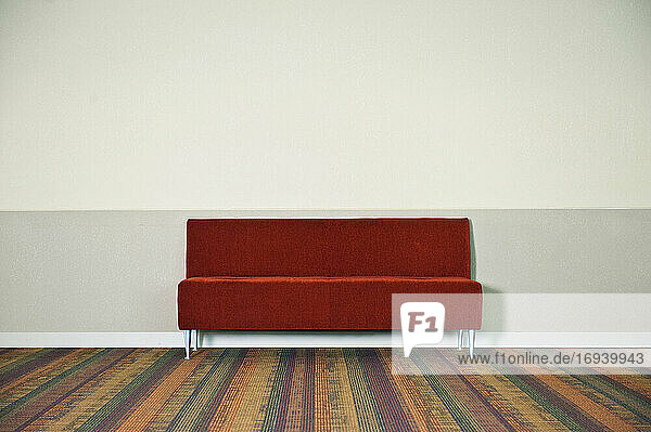 Red sofa on striped carpet.