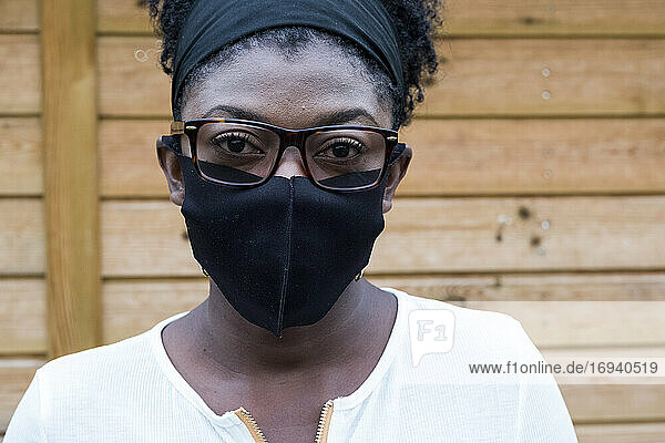 Portrait of black woman wearing glasses and face mask  looking at camera.
