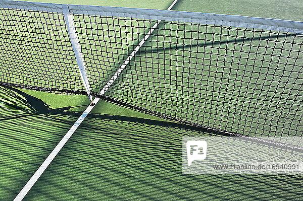 Tennis net lifted on tennis court.