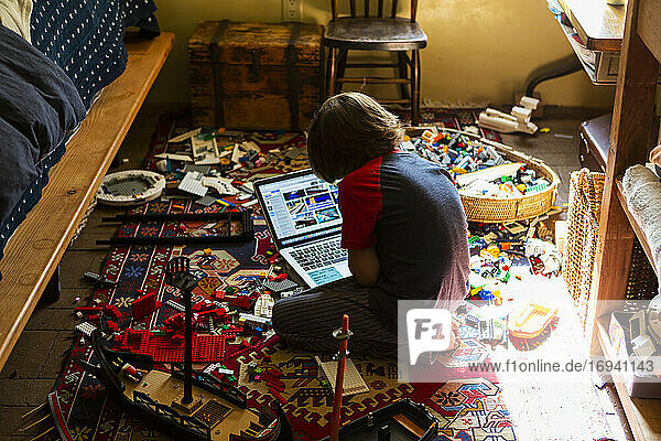 Young boy playing in his room  looking at laptop